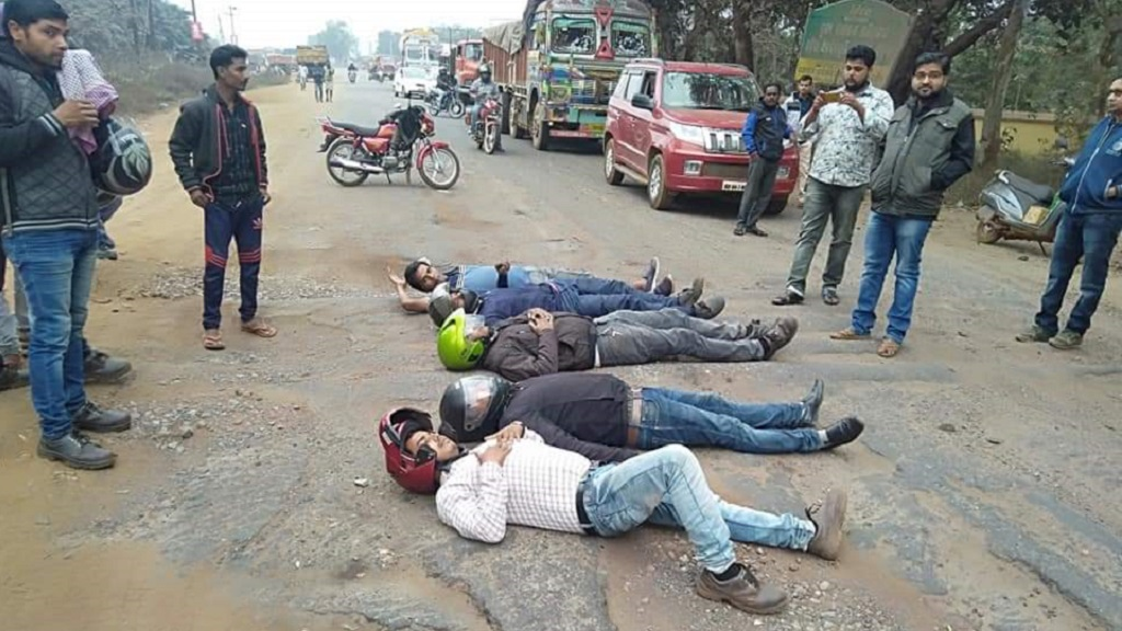 People lay on road wearing helmet to protest bad road condition